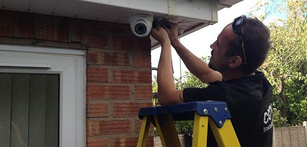 CCTV installation engineer fitting a camera to a house